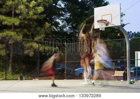 Lawrenceville GA USA - May 27 2016: Motion blur of young men playing a pickup game of basketball at a public park on May 27 2016 in Lawrenceville GA.
