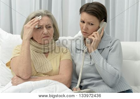 ill Senior woman with caring worried daughter  with phone
