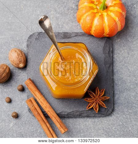 Pumpkin confiture, jam, sauce with spices on stone table Top view.