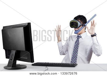 Image of a shocked worker looking at the monitor while wearing goggles and snorkel isolated on white background