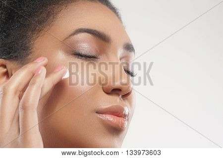 Close up of face of pretty young mulatto woman applying cream on her check. Her eyes are closed with enjoyment. Isolated and copy space in right side