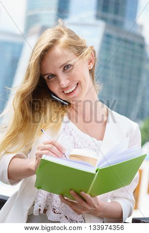 Businesswoman taking notes white talking by phone and drinking coffee