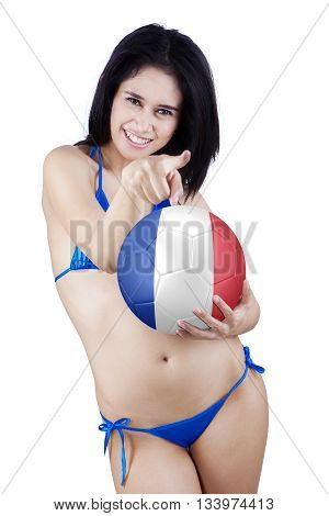 Portrait of beautiful young woman wearing bikini pointing at camera while holding a soccer ball with flag of France isolated on white background