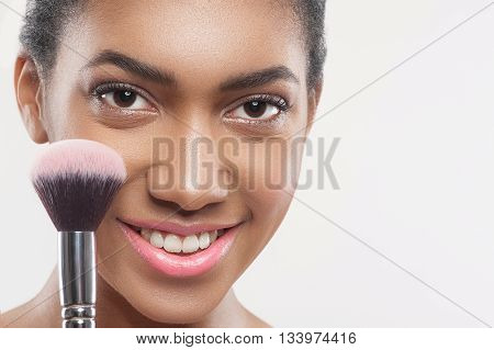 Portrait of attractive mulatto girl touching a brush with blusher to her cheek. She is looking at camera and smiling. Isolated and copy space in right side