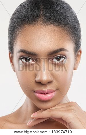 Portrait of beautiful mulatto girl caring of her skin. She is standing and touching her chin gently. The lady is looking at camera with confidence. Isolated