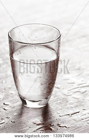 Filled glass of water on wooden background