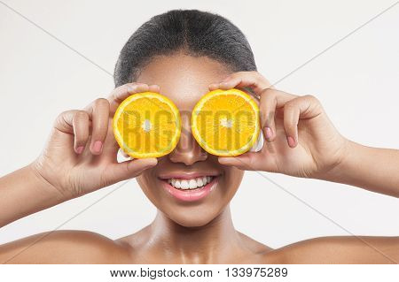 Cheerful young mulatto woman is covering her eyes with pieces of orange. She is standing and smiling. Isolated