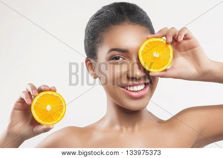 Portrait of beautiful african girl caring of her skin. She is standing and holding a piece of orange. The lady is covering her eye with fruit and laughing. Isolated