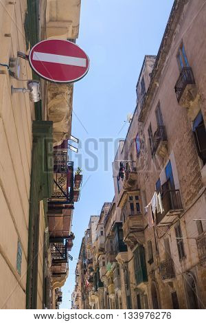 One of many narrow streets in the capital of island Malta - Valletta. View on the windows and balconies. No entry sign in the foreground.