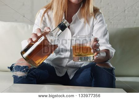 blond sad and wasted alcoholic woman sitting at home sofa couch drinking and filling glass pouring scotch whiskey from bottle depressed lonely and suffering hangover in alcoholism and alcohol abuse