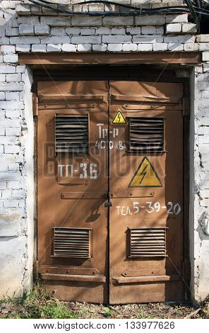 old metal brown doors of old white brick building of transformer sunstation with yellow signs of electrical zahard