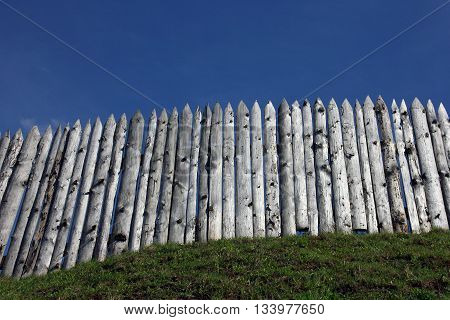 the wooden palisade on the green grass shaft of the ancient fortress and city and blue sky as a background Torzhok Russia