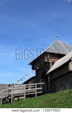 old russian traditional historical wooden log fortress tower with entrance gates and colorful flags on a rope and green grass with blue sky Torzhok Russia
