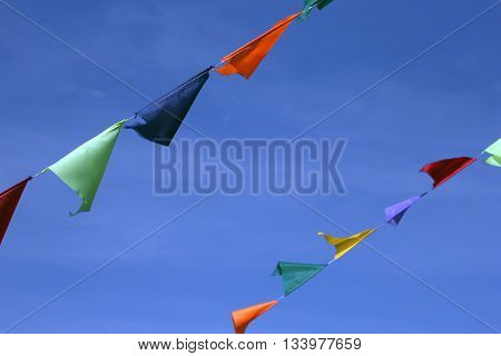 multi colored small triangular fair flags on a rope on a blue sky background