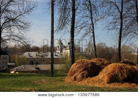 russian provincial landscape - golden haystack in the green meadow in the background of provincial old russian town and trees Torzhok Russia