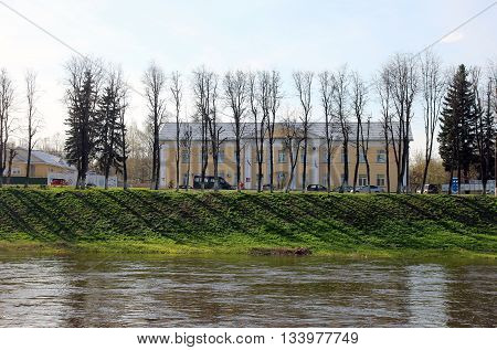 City view - old yellow building on the waterfront on the green bank of river Tvertsa with line of trees Torzhok Russia
