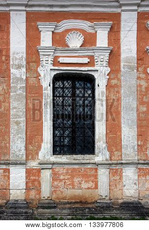facade wall from limestone brick blocks with window with bars of old abandoned medieval russian orthodox church in old russian style near Staritsa Russia