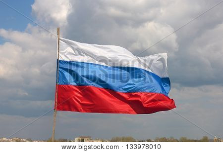colorful bright beautiful state flag of Russia (Russian Federation) waving on the wind on blue sky background with white clouds