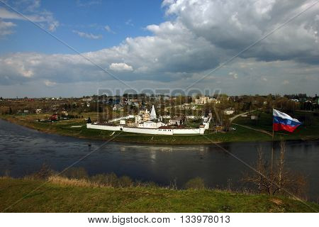 beautiful panoramic view from hill to old ancient orthodox white monastery on the other side of river and russian state flag on the hill Staritsa Russia