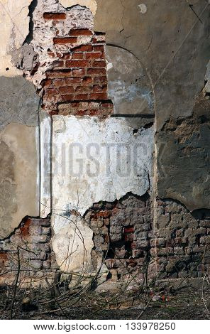 old ruined red brick wall of church with loose cracked white and brown plaster