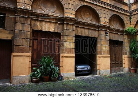 unusual interesting old medieval private car garages in the italian courtyard patio with oak wooden gates Rome Italy