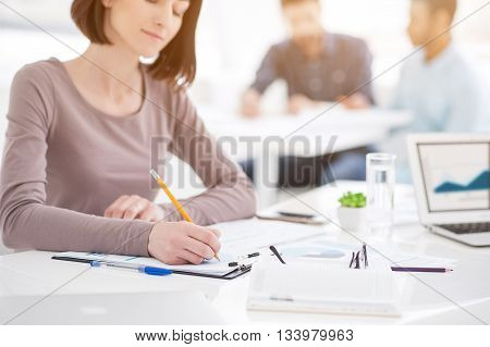 Teamwork in action. Close up of young office worker sitting at table with colleagues in the background and making notes in notebook