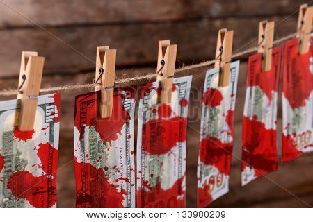 Concept of money laundering - dollars with bloodstains are drying on cord on wooden background, close up