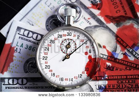 Stopwatch and dollar banknotes with bloodstains on black background.