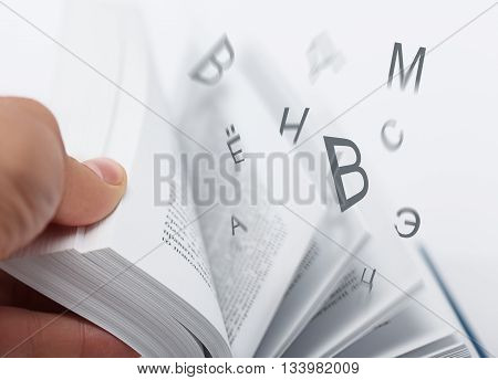 Letters flying with flipping book pages. Low aperture shot selective focus. Education reading dictionary concept.