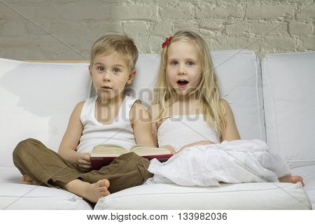 two Happy children read a interesting book
