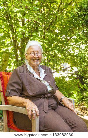 senior woman enjoys sitting in her garden