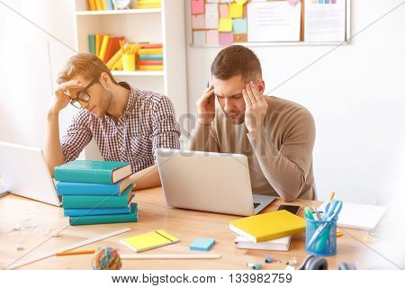 Student stress. Two guys tired and holding their hands behind their head, sitting at laptop