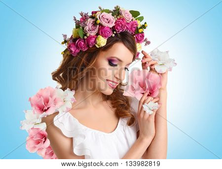 Beautiful young woman wearing floral headband with beautiful flowers on blue background