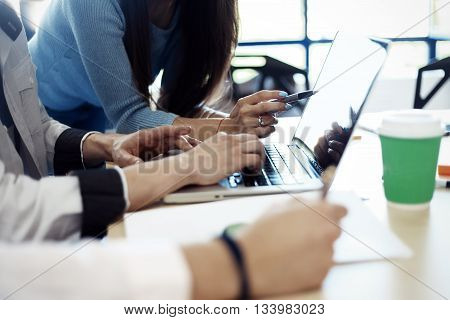 Business meeting concept. Photo young businessmans crew working with new startup project in modern loft. Generic design smartphone holding female hands.