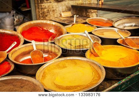 Close-up of different spices in bowls to prepare delicious food. The counter on the Mahane Yehuda Market in Jerusalem, Israel.