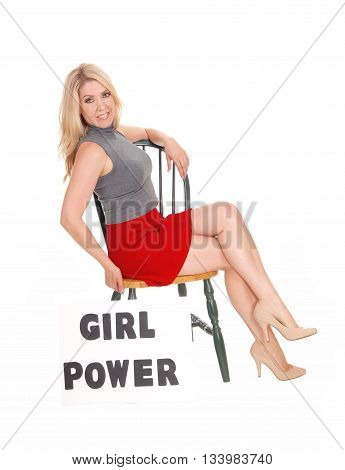A lovely blond woman sitting on a chair in a red skirt and gray weather with a sign