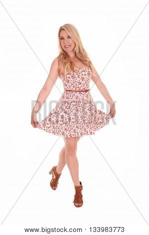 A lovely woman with long blond hair standing in a summer dress isolated for white background lifting up her dress.