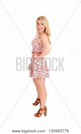 A lovely woman with long blond hair standing in a summer dress isolated for white background.