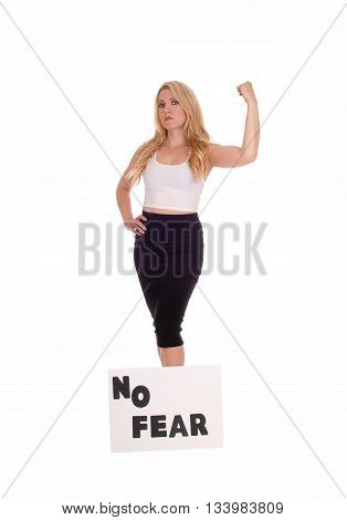 A serious gorgeous blond woman standing in a black skirt with her muscles fleshed with a sign NO FEAR isolated for white background.