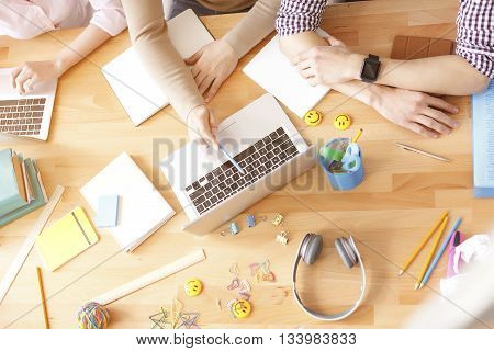 Colleagues using laptop. Top view of hands of group of workers sitting at office desk and using digital tablets, notebooks and various objects all around