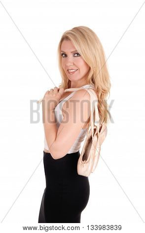 A closeup image of a gorgeous young woman in a black skirt with her ballet shoes over her shoulder isolated for white background.