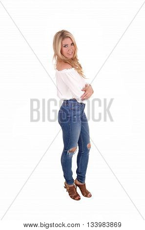 A gorgeous young blond woman standing in jeans and white blouse in profile isolated for white background.