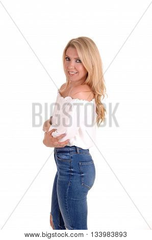 A very pretty young blond woman standing half length in a white blouse and jeans in profile isolated for white background.