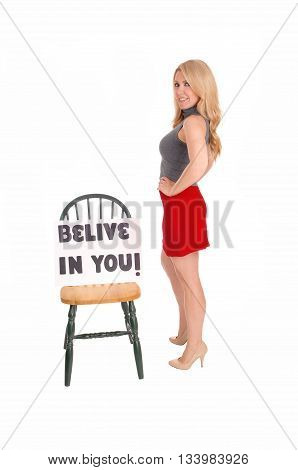 A lovely blond woman in a red skirt and gray sweater standing with a sign