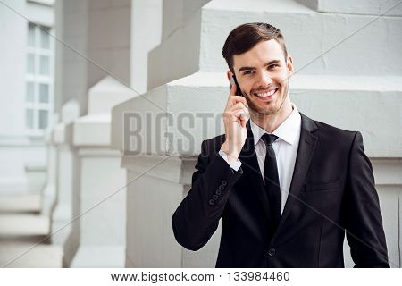 Positivity in mind. Cheerful delighted handsome man smiling and talking on cell phone while standing near the wall