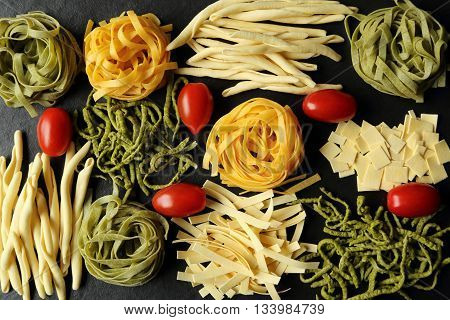 Various types of pasta on a black ceramic background.