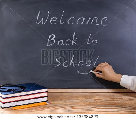 Teacher hand putting smile symbol on welcome message to students on erased black chalkboard. Desktop with books pencils and reading glasses in forefront.