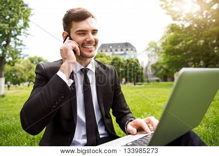 Always in touch. Positive smiling handsome man sitting on the grass and using laptop while talking on cell phone