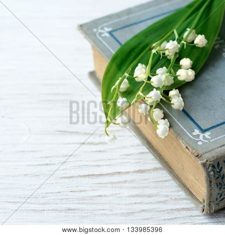 Old book with bouquet of the lilies of the valley, nostalgic vintage background