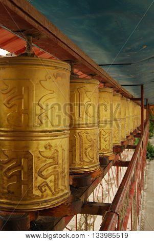 GYANTSE, TIBET, CHINA - AUGUST 4, 2010: row of prayer wheels at Pelkor Chode Monastery (Palcho Monastery)